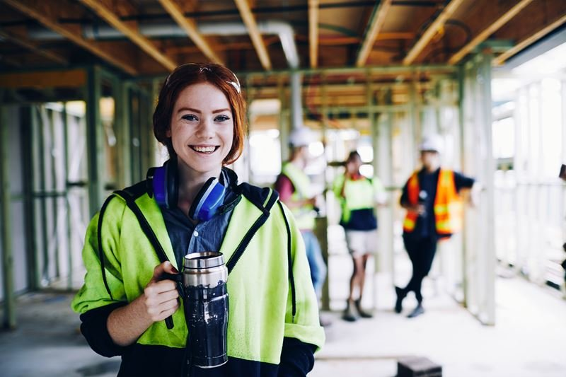 Happy female construction worker with team behind her - BUSSQ Super